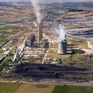 Fossil fuel power plant & coal piles, aerial view