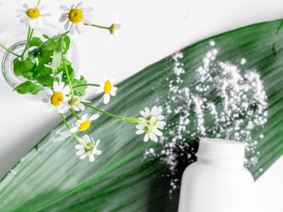natural organic cosmetics for baby with chamomile on white background top view